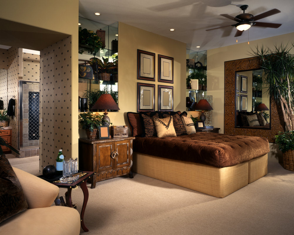 This master bedroom features stylish walls and carpet floors. It has its own bathroom. It also features a classy bed and multiple indoor plants.
