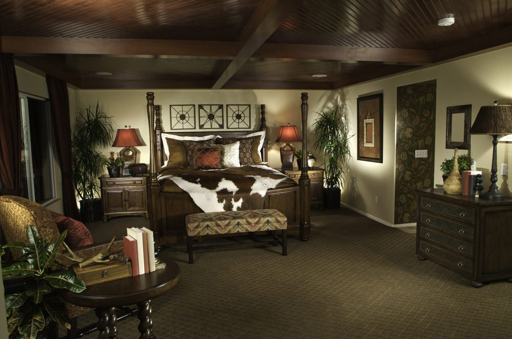 This master bedroom boasts stylish carpet flooring and a luxurious-looking bed under the stunning ceiling.
