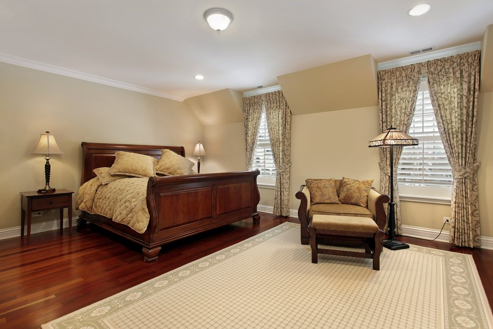 Cozy primary bedroom showcases a hardwood flooring topped with a floral border area rug. It has glass windows framed with white blinds and covered in patterned curtains.
