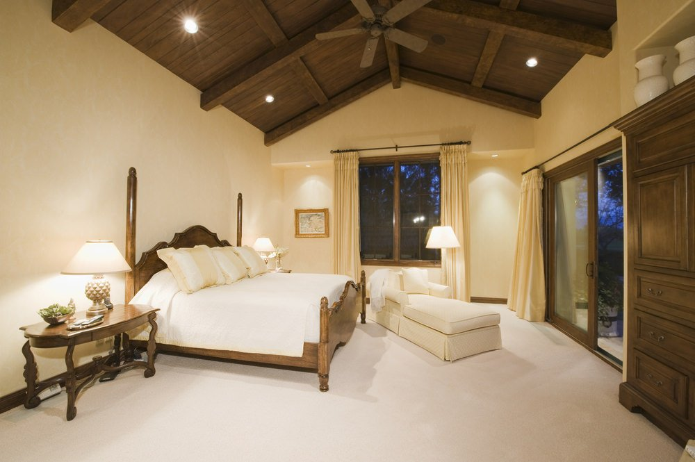A master bedroom with white floors, beige walls and a tall wooden vaulted ceiling with recessed lights.