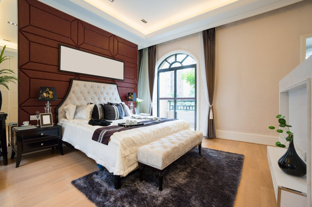 White tufted bed with a matching bench on its end lays on an eye-catching brown accent wall designed with a rectangular mirror. It features an arched paneled window that brings natural light in.