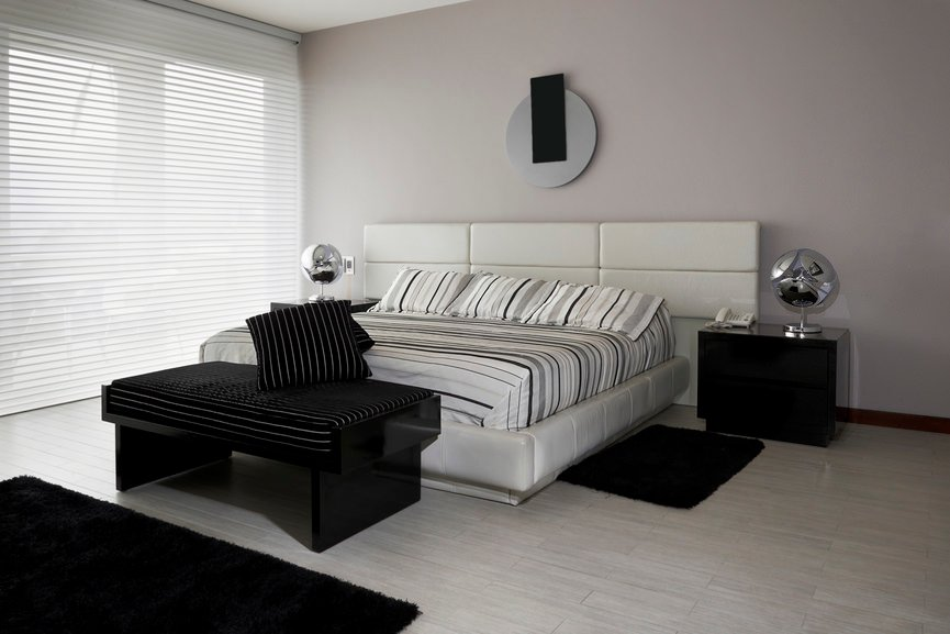 Contemporary master bedroom with a black shade that looks absolutely stunning and elegant. The gray walls look perfect together with the room's style.