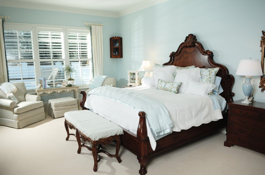 This primary bedroom features sky blue walls and a classy bed set on the room's carpet flooring.