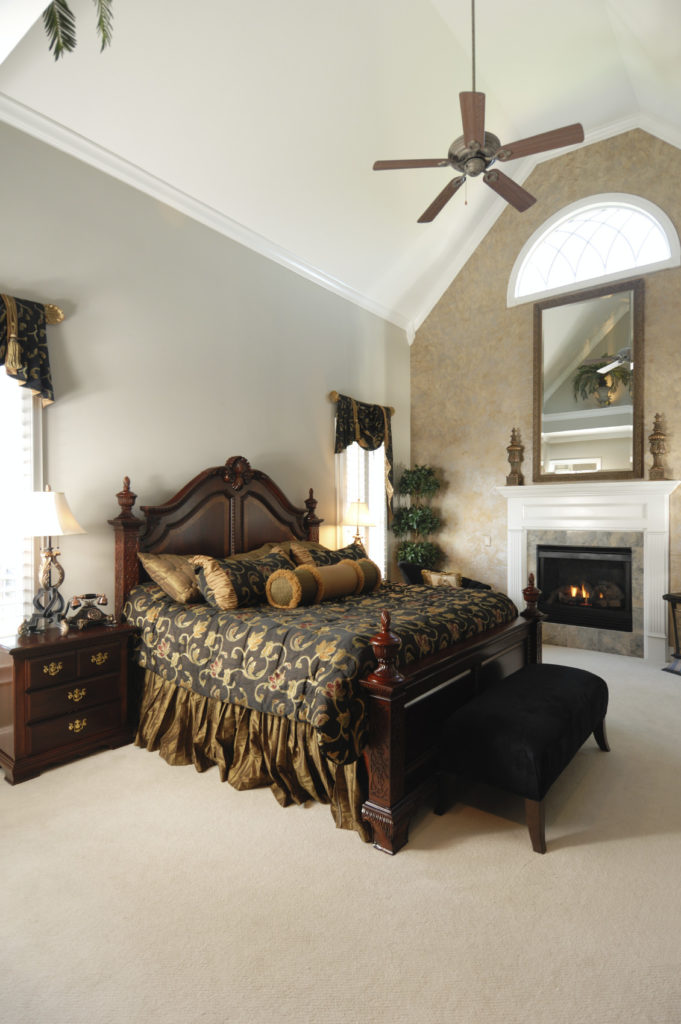 A primary bedroom with a luxurious bed, carpet floors and a fireplace, along with a tall ceiling.