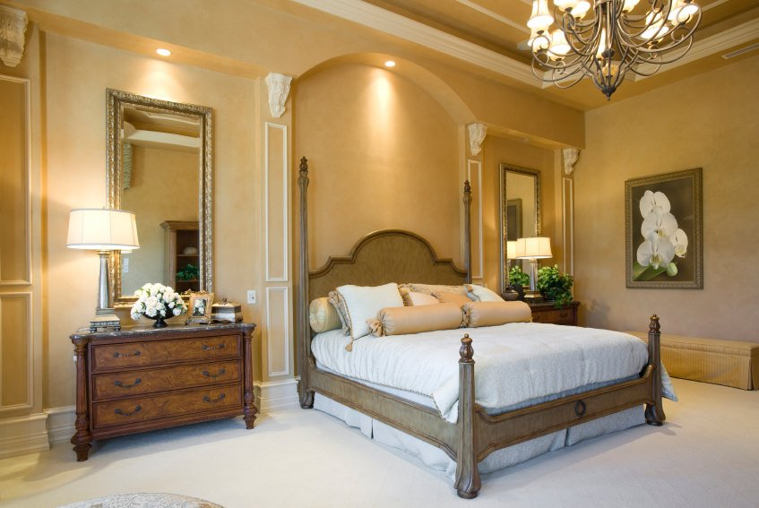 This master bedroom is designed with floral wall art that hung above the skirted bench facing the wooden bed in between nightstands that are paired with ornate mirrors.