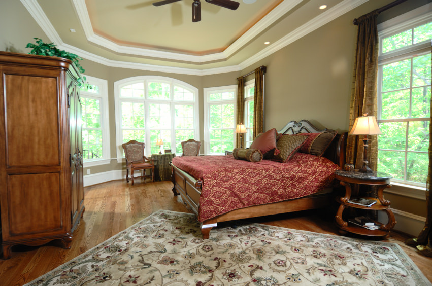 Large master bathroom boasting a classy large bed set on the hardwood flooring topped by a classy rug.