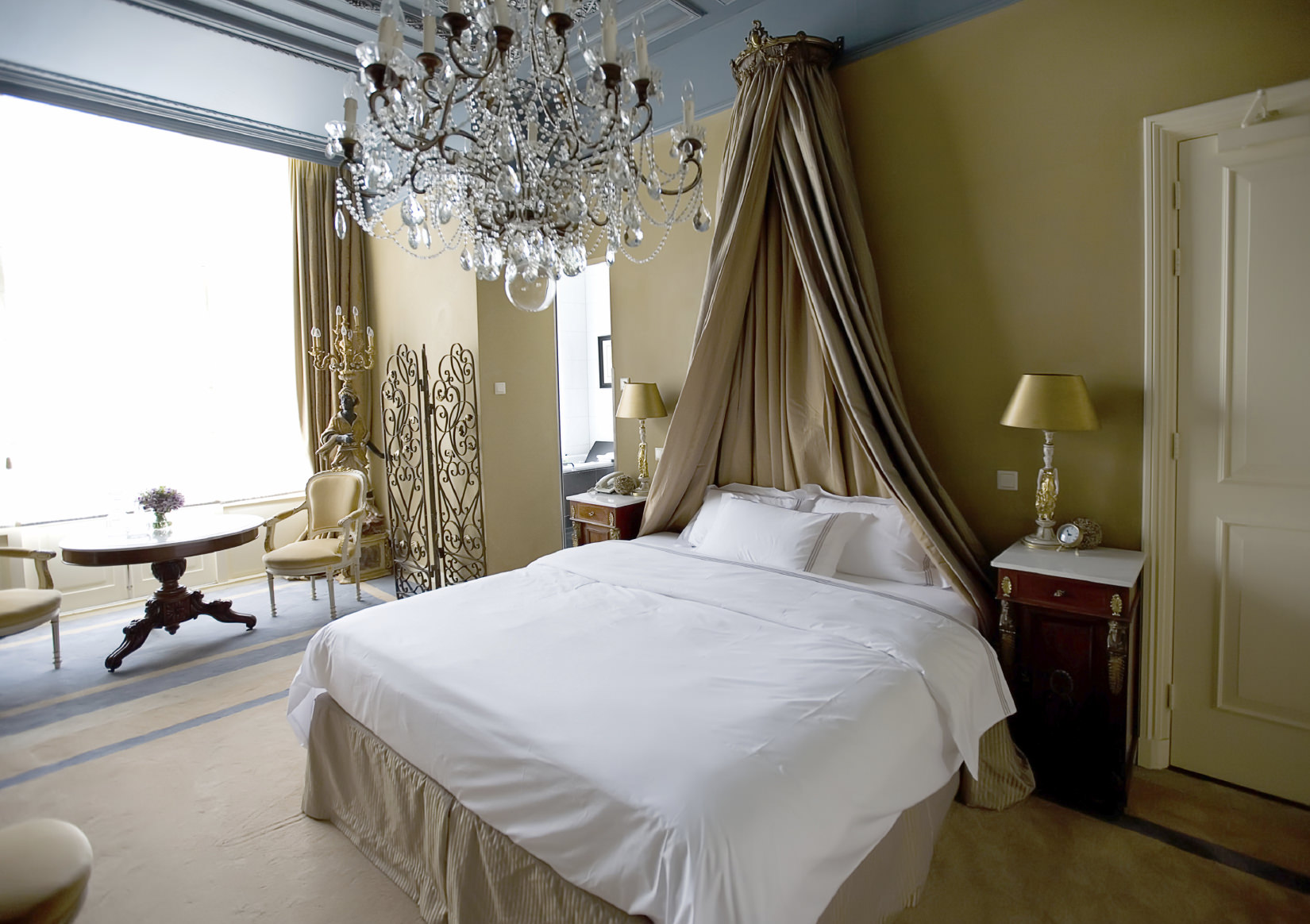 A gorgeous primary bedroom offers a comfy bed lighted by an oversized crystal chandelier that hung from the bluish gray ceiling.