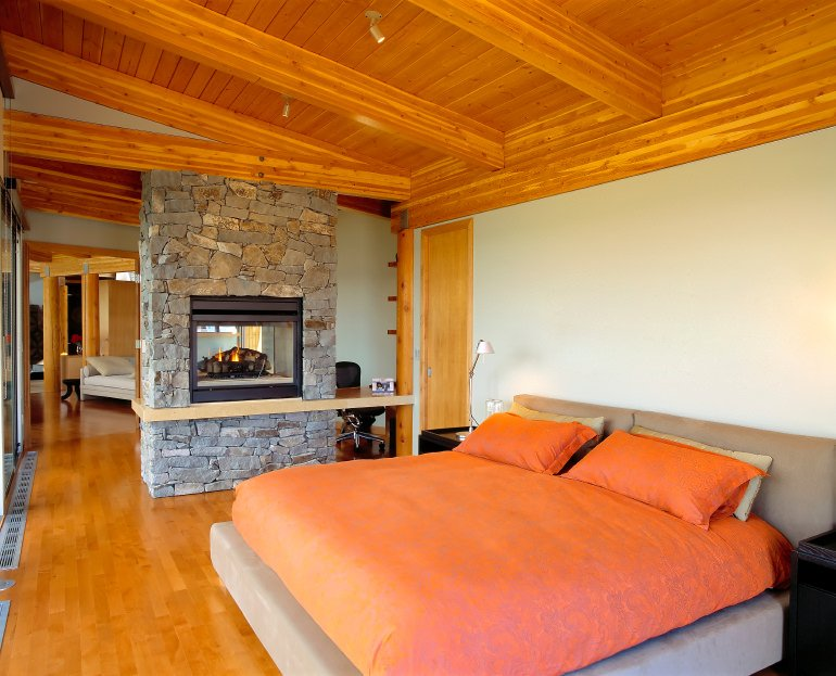 Primary bedroom features a shiplap wall with exposed wood beams complementing the hardwood flooring. It includes a taupe bed dressed in orange bedding across a fireplace mounted on a brick pillar.