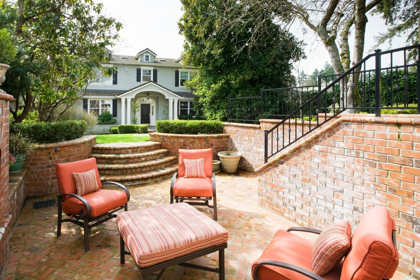 This home offers a stunning classy patio area featuring cozy seats surrounded by beautiful trees.