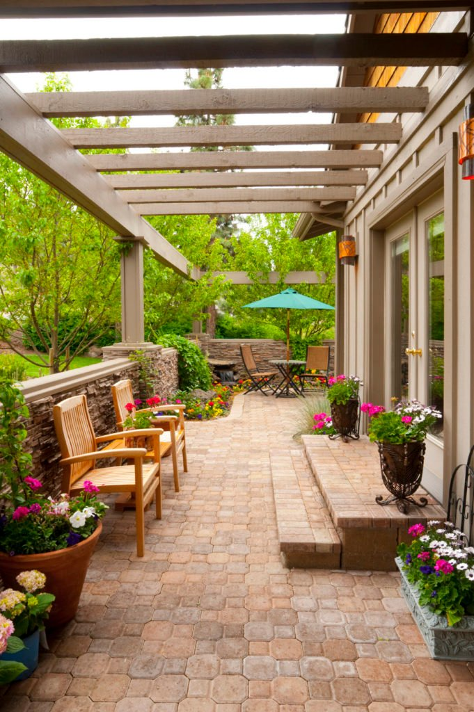 Narrow hallway featuring a patio area on the corner surrounded by beautiful and colorful flowers.