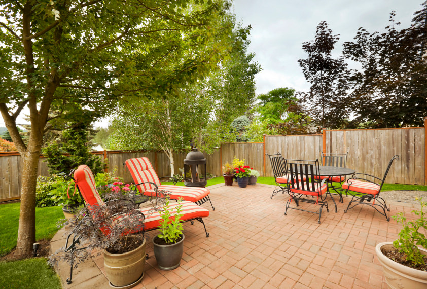 This small patio area features a cozy lounger seats with a center table along with the four-seat dining table set.