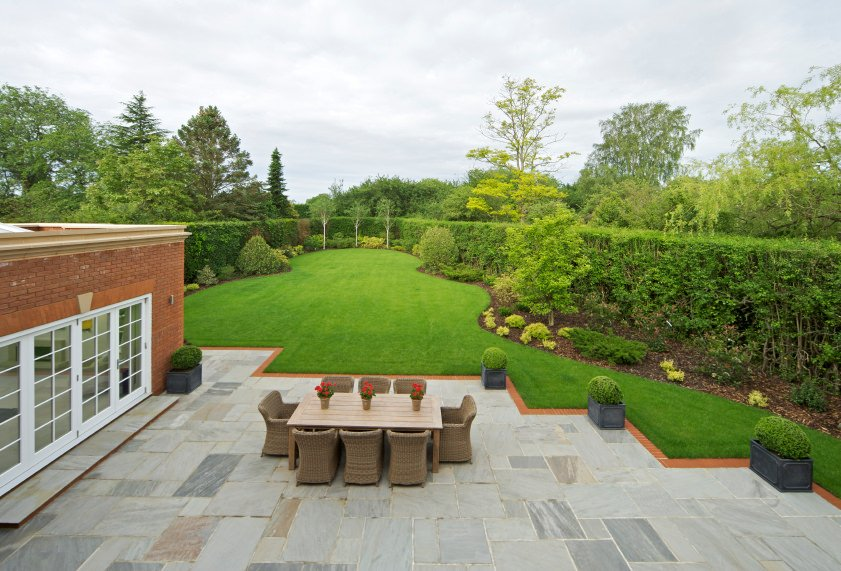 This backyard looks stunning. The wide garden is so beautiful while the walkway provides a dining table set near the home's door.
