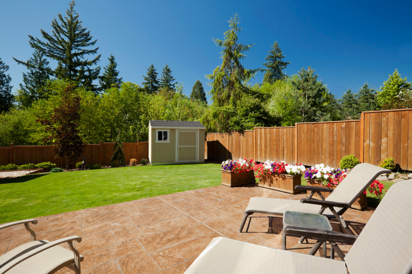 This backyard offers a lovely patio and a lawn area. There are colorful lovely flowers next to the patio area.