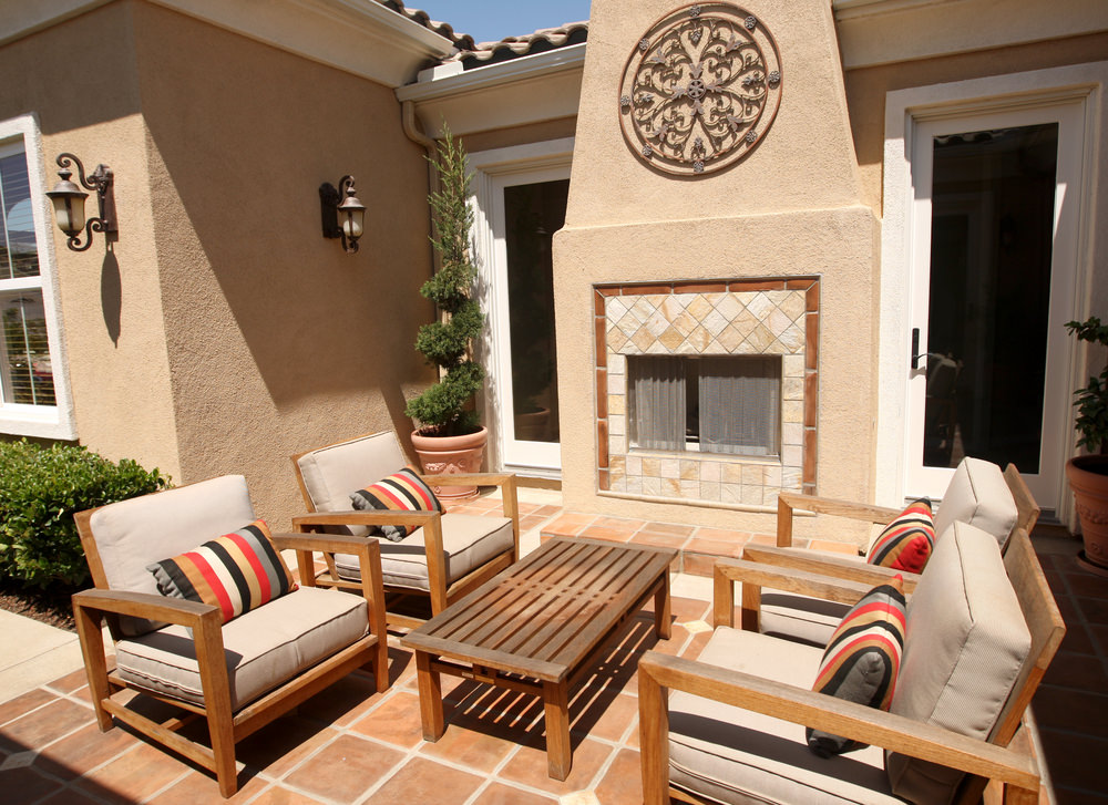 Small patio area featuring wooden seats with cushion seating and back rests along with a small center table near the fireplace.