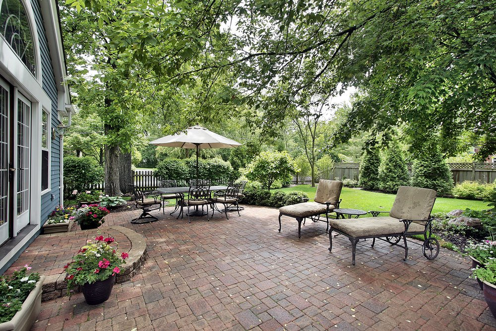 Large patio area featuring a dining table set and a couple of lounger seats surrounded by a beautiful greenery.