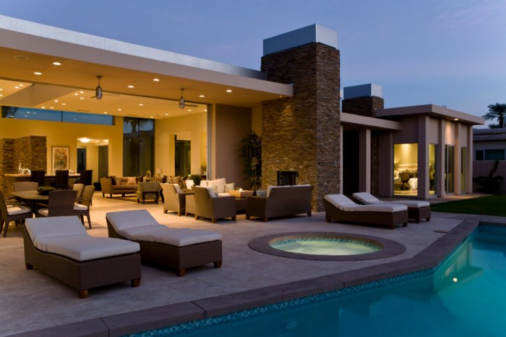 This pool side patio offers multiple table sets and lounger seats.