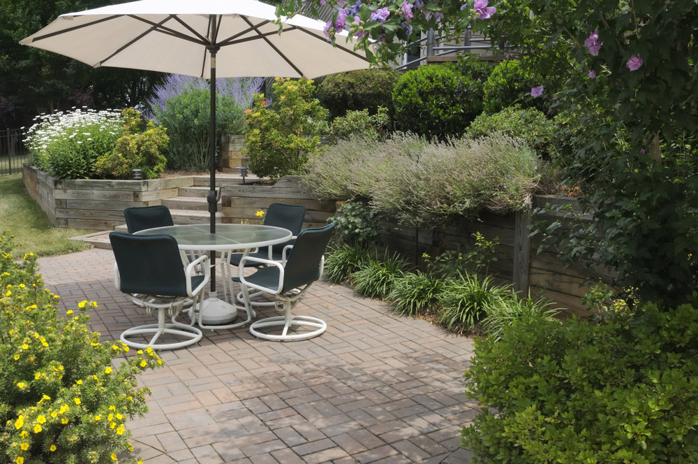 This patio area offers a small dining table set surrounded by lovely plants.