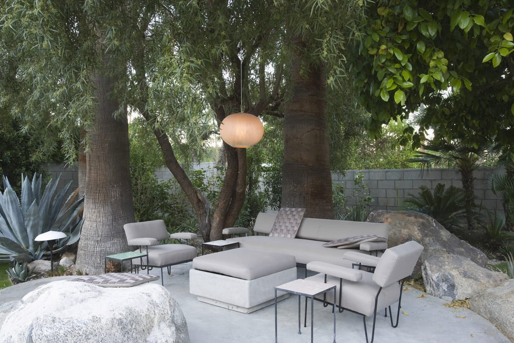 This patio offers a modern cozy outdoor living set with a pendant light hanging from the tree.