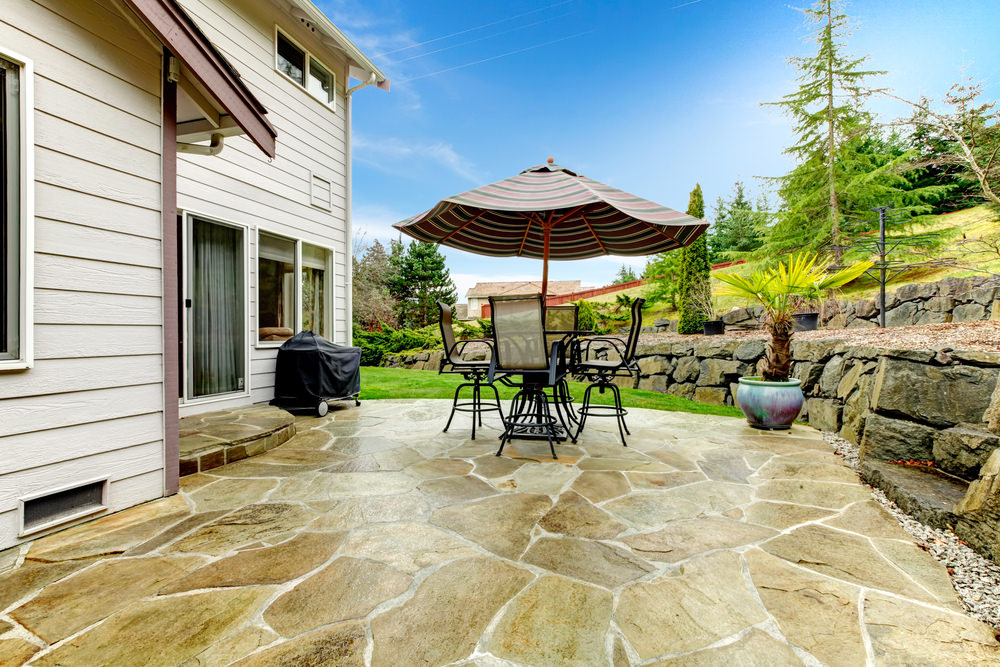 This patio features a small dining table set shaded by a charming umbrella.