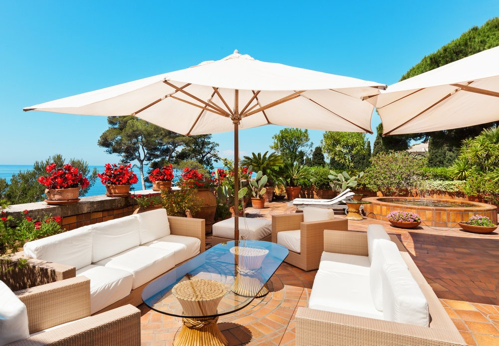 This lovely patio offers a comfortable set of seats shaded by beautiful umbrellas and surrounded by gorgeous plants and greens.