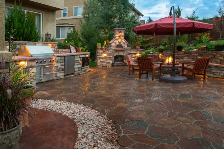 Large patio with charming lights and flooring. There's also an outdoor kitchen.