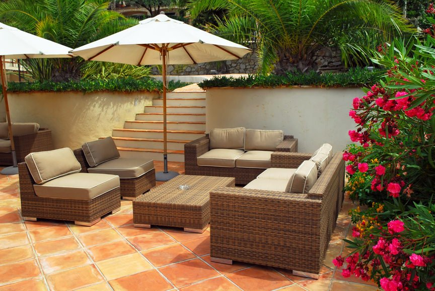 This patio offers a great view of flowers and green plants all over the place while relaxing on a set of rattan seats.