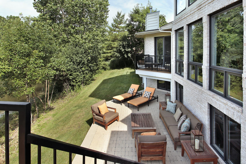 This mansion offers a patio area with comfortable seats and a couple of loungers overlooking the river.