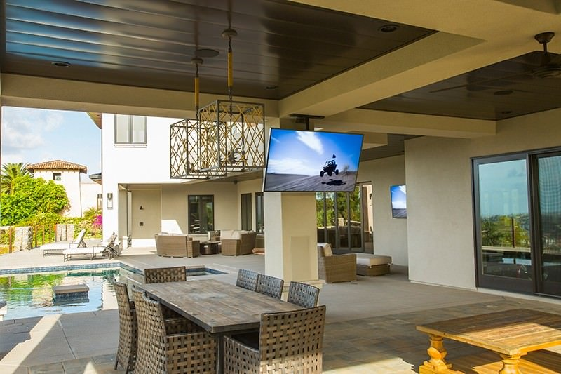 Pool side patio area with a wide screen TV and a dining table set.