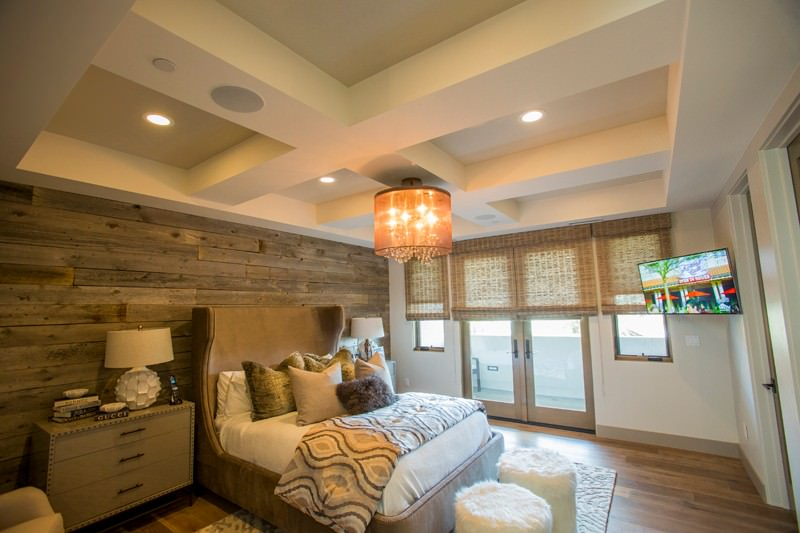 A fancy semi-flush light mounted on the coffered ceiling illuminates this guest bedroom boasting brown wingback bed with furry stools on its end.