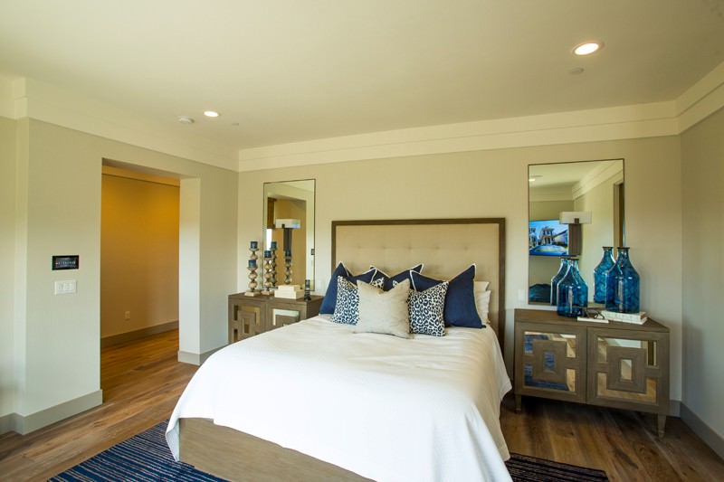 Beige guest bedroom accented with blue pillows, striped area rug and translucent jars that sit on a stylish mirrored nightstand.