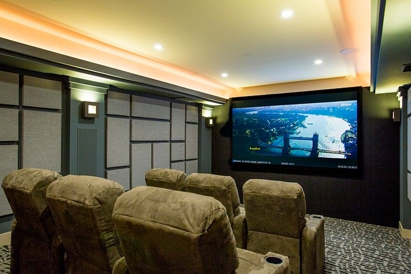 This home theater boasts a jaw-dropping brightceiling along with stylish walls and wall lights.