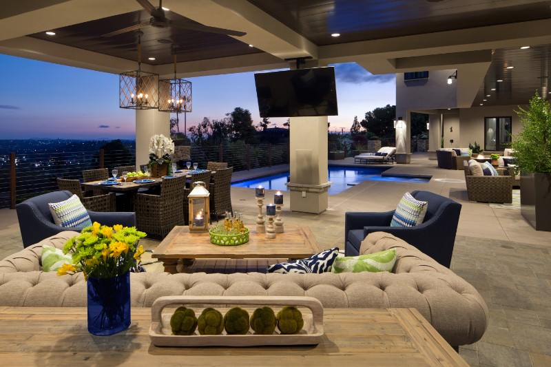 Modern mansion offering a nice patio area with a wide TV screen and a dining table set near the pool.