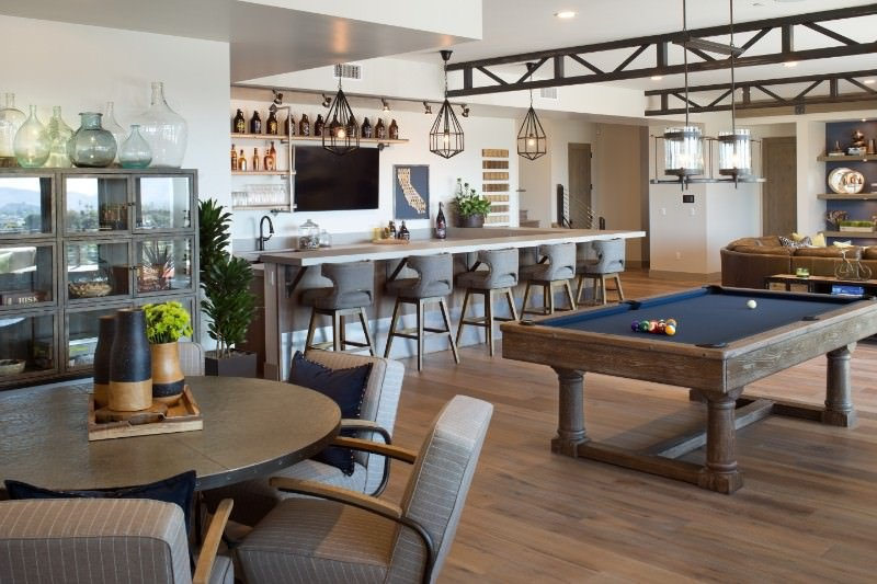 This living room features a large bar and a billiards pool, along with a dining nook set on the hardwood flooring and lighted by glamorous pendant lights.