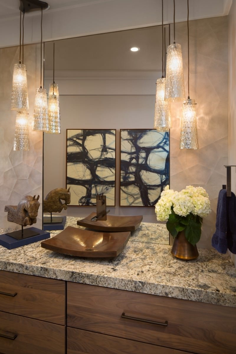 Fabulous bathroom illuminated by fancy pendants that hung over a wooden vessel sink vanity topped with a marble counter.