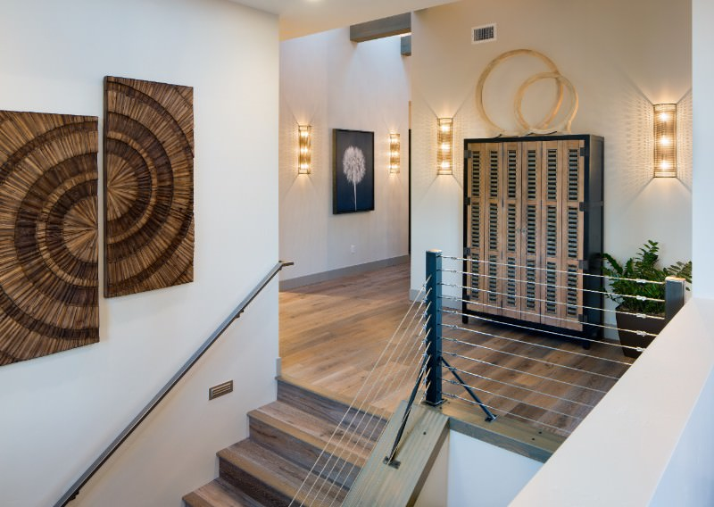 This foyer offers a handful of stunning wall decors. The flooring fits well with the white walls and wall lighting.