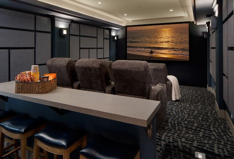 This contemporary home theater features stylish wall design and carpet flooring. The sectional seats are perfectly placed and lighted by wall lights and recessed lighting.