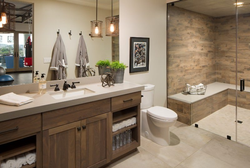 Mid-sized bathroom showcases a walk-in shower with seating and glass door. It includes a toilet next to the wooden sink vanity with built-in shelving and granite countertop.