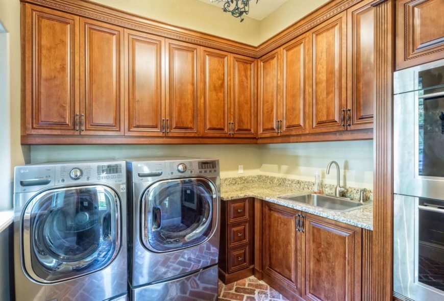 The cherry-finished cabinetry and sink counter add class to this small laundry room.