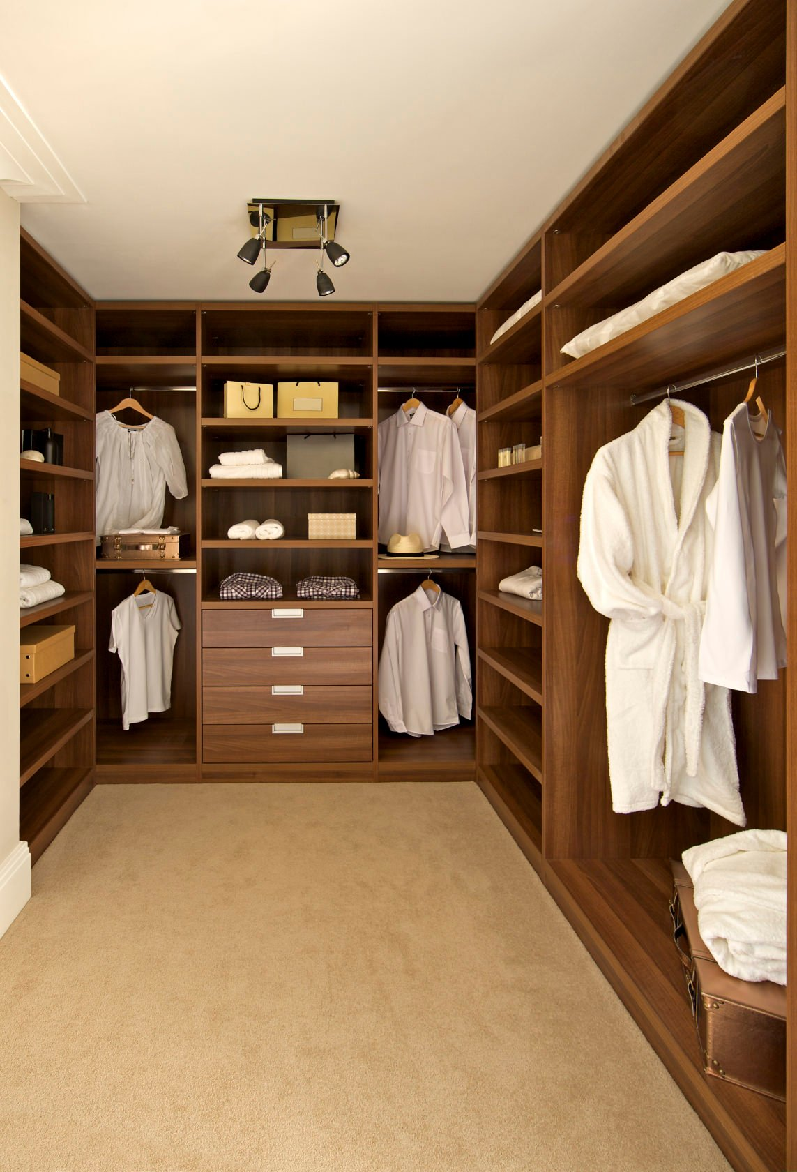This men and women's modern closet features brown cabinets and a carpet flooring lighted by a set of track ceiling lights.