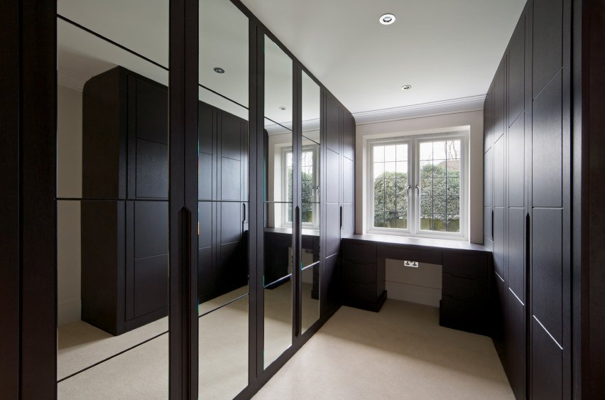 Modern closet featuring espresso finished cabinets with mirror doors.