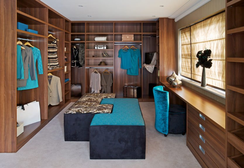 This walk-in wardrobe design comprises of certain elements that take it to a whole different level. The built-in desk by the window is best of pensive people while the coral and deep blue suede seating arrangement lets you sit back and relax.