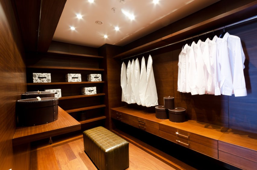 This walk-in closet from a house in Japan is ideal for professionals who own a lot of white clothes as they will balance well against the deep chocolate wooden interior.