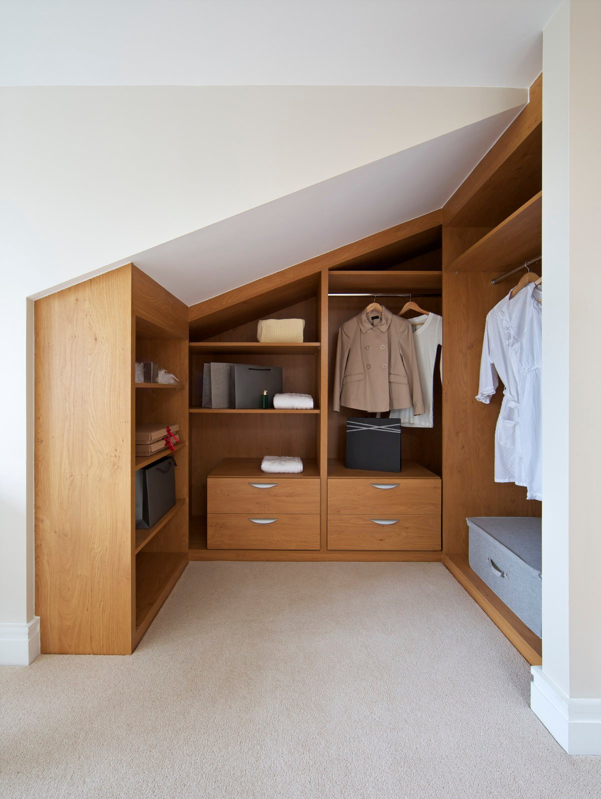 This modern women's closet features walnut finished cabinets set on a carpet flooring.
