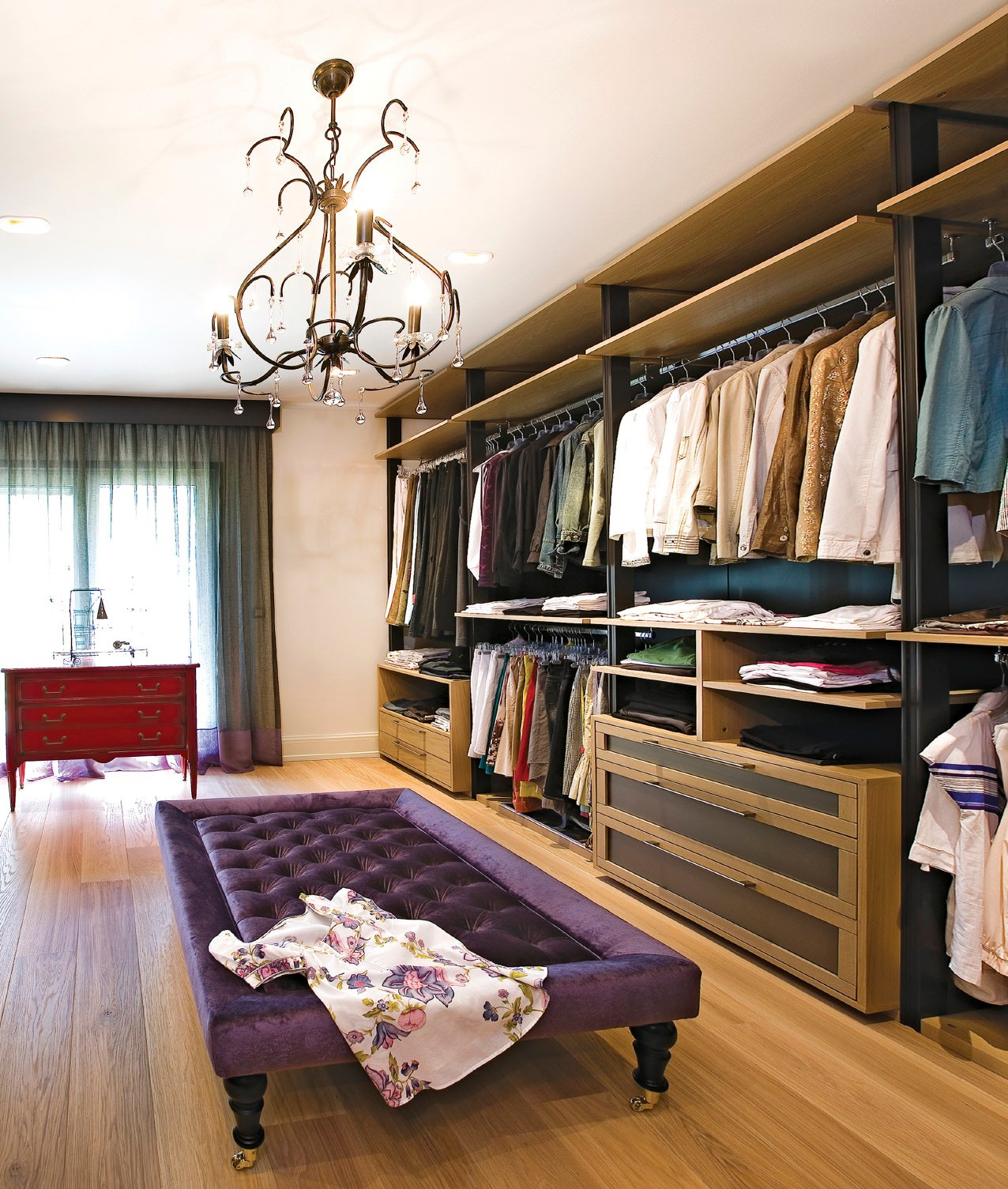 This bedroom closet features a hardwood flooring matching the cabinetry. The gorgeous chandelier lights up the room.