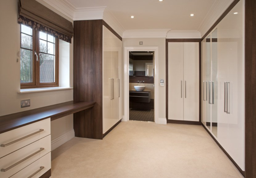 This closet with white and brown color combination looks great with the carpet flooring and recessed ceiling lights.