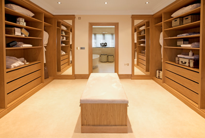 This bright modern closet is accessible from the home's bathroom. The walnut finished cabinets surrounds the space. The carpet flooring matches the white walls.