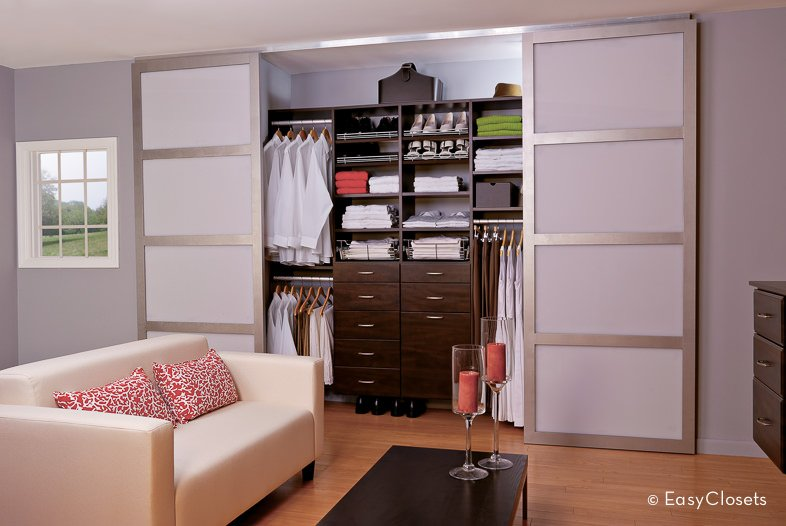 This modern women's closet is located just inside her room. It has sliding doors and brown finished cabinets.