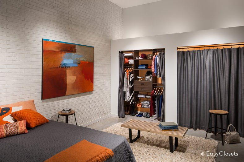Small bedroom closet featuring a brown cabinetry with gray curtains.