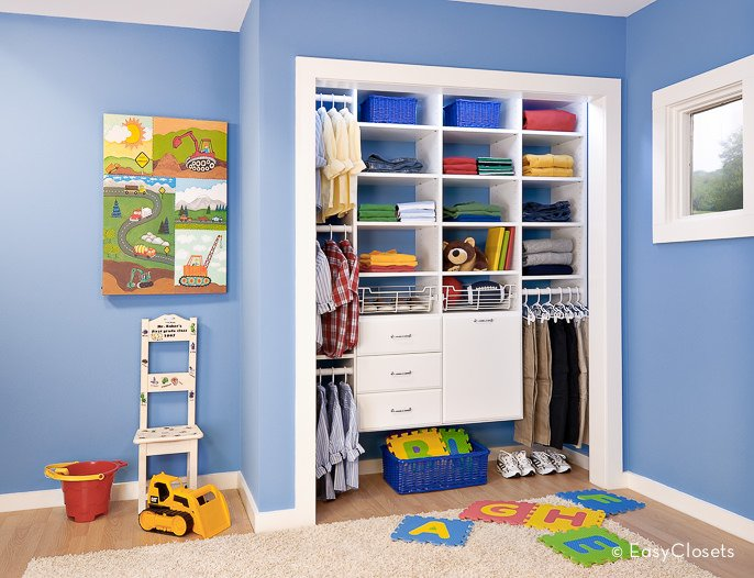 Small bedroom closet for kids featuring white cabinetry.