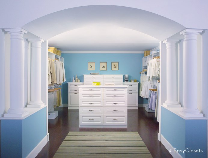 This bedroom closet offers a combination of blue and white colors. The blue walls blend well with the white ceiling and cabinetry. There's an arch hallway adding style to the room.